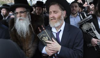 Community members, including Rabbi Chaim Rottenberg, left, celebrate the arrival of a new Torah near the rabbi's residence in Monsey, N.Y. A day earlier, a knife-wielding man stormed into the home and stabbed multiple people as they celebrated Hanukkah in the Orthodox Jewish community. (AP Photo/Craig Ruttle)