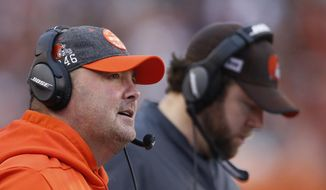 Cleveland Browns head coach Freddie Kitchens, left, watches during the first half of an NFL football game against the Cincinnati Bengals, Sunday, Dec. 29, 2019, in Cincinnati. (AP Photo/Gary Landers)