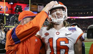 Clemson quarterback Trevor Lawrence (16) is congratulated after Clemson defeated Ohio State 29-23 in the Fiesta Bowl NCAA college football playoff semifinal Saturday, Dec. 28, 2019, in Glendale, Ariz. (AP Photo/Ross D. Franklin) **FILE**