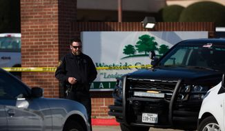 An officer stands near the scene after a church shooting at West Freeway Church of Christ on Sunday, Dec. 29, 2019 in White Settlement, Texas. (Juan Figueroa/The Dallas Morning News via AP)