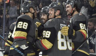 Vegas Golden Knights left wing William Carrier (28), defenseman Nate Schmidt (88), right wing Mark Stone (61) celebrate a goal by center Chandler Stephenson, second left, against the Arizona Coyotes during the second period of an NHL hockey game Saturday, Dec. 28, 2019, in Las Vegas. (AP Photo/David Becker)