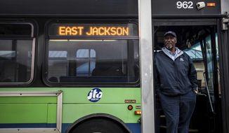 Tony Neely, 60, stands at the door of his Jackson Transit Authority bus on Dec. 17, 2019 in Jackson, Tenn. (Stephanie Amador/Jackson Sun via AP)