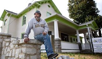 In this August 2018 photo , Sam Pass sits on a retaining wall of the 1889-era Magnolia House in Greensboro, N.C., which he restored. Pass, at one time a fire and safety specialist at Duke University, had spent the past two decades of his off time meticulously restoring the historic hotel. (H. Scott Hoffmann/News & Record via AP)