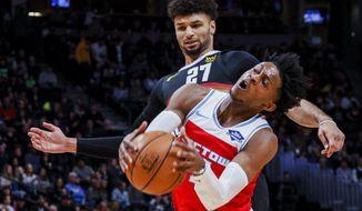 Sacramento Kings guard De'Aaron Fox (5) collides with Denver Nuggets guard Jamal Murray (27) in the first half of an NBA basketball game Sunday, Dec. 29, 2019, in Denver. (AP Photo/Joe Mahoney)