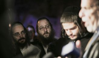Orthodox Jewish people listen to N.Y. state Assemblyman Dov Hikind speak in Monsey, N.Y., Sunday, Dec. 29, 2019, following a stabbing late Saturday during a Hanukkah celebration. A man attacked the celebration at a rabbi's home north of New York City late Saturday, stabbing and wounding several people before fleeing in a vehicle, police said. (AP Photo/Allyse Pulliam)