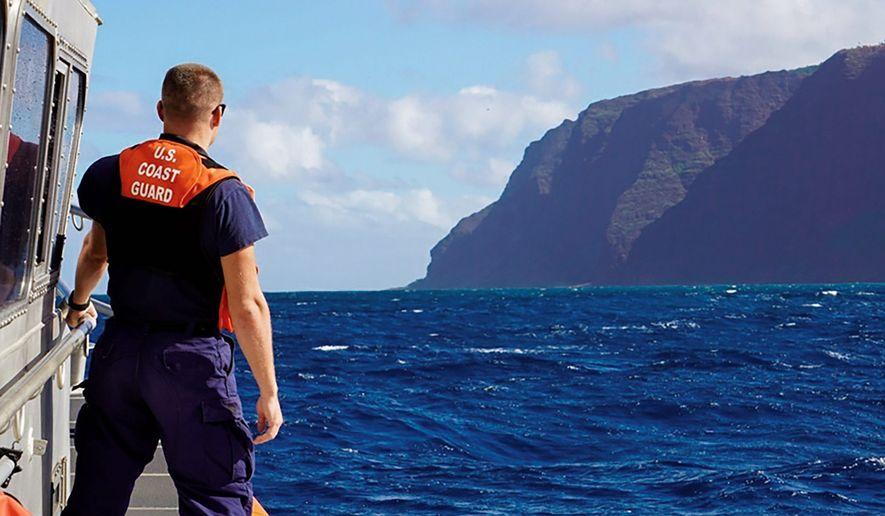 A Coast Guard vessel moves toward the Na Pali Coast on the Hawaiian island of Kauai after a tour helicopter crashed with seven people aboard. (U.S. Coast Guard via Associated Press)