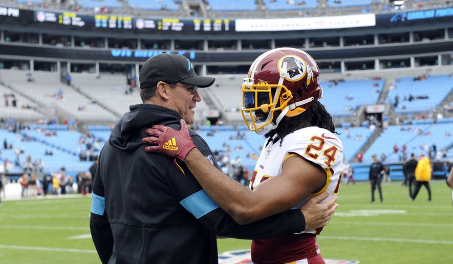 Carolina Panthers head coach Ron Rivera and Washington Redskins cornerback Josh Norman (24) speak prior to an NFL football game in Charlotte, N.C., Sunday, Dec. 1, 2019. (AP Photo/Mike McCarn) **FILE**