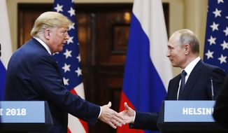 In this photo taken on Monday, July 16, 2018, U.S. President Donald Trump shakes hand with Russian President Vladimir Putin at the end of the press conference after their meeting at the Presidential Palace in Helsinki. (AP Photo/Alexander Zemlianichenko) **FILE**
