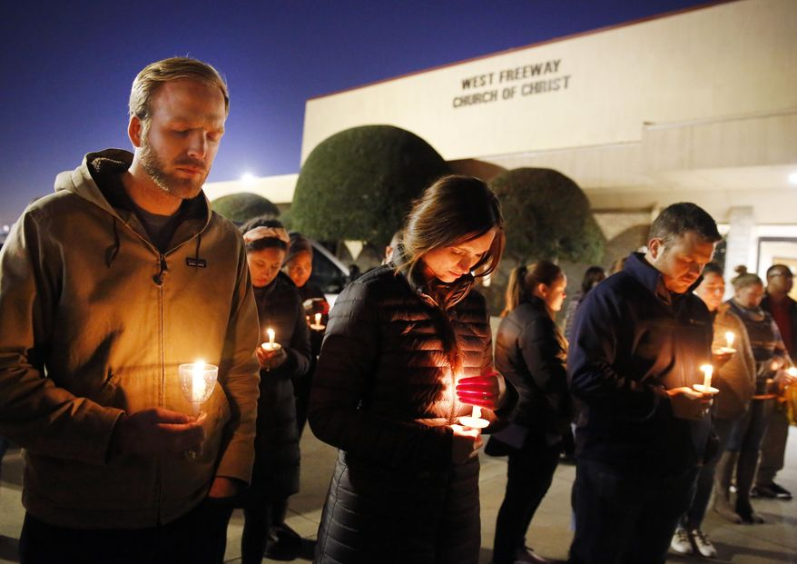 Church and community members, including Matt Pacholczyk, left, and his wife, Faith Pacholczyk, stand outside West Freeway Church of Christ for a candlelight vigil, Monday, Dec. 30, 2019, in White Settlement, Texas. A gunman shot and killed two people before an armed security officer returned fire, killing him during a service at the church on Sunday. (Tom Fox/The Dallas Morning News via AP)