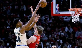 Milwaukee Bucks forward Giannis Antetokounmpo (34) shoots over Chicago Bulls forward Lauri Markkanen (24) during the first half of an NBA basketball game, Monday, Dec. 30, 2019, in Chicago. (AP Photo/Matt Marton)