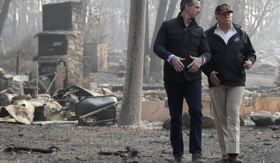 FILE - In this Nov. 17, 2018, file photo, President Donald Trump talks with then California Gov.-elect Gavin Newsom during a visit to a neighborhood destroyed by the wildfires in Paradise, Calif. Gov.  Newsom is wrapping up a first year highlighted by the bankruptcy of the country's largest utility, an escalating homelessness crisis and an intensifying feud with the Trump administration, along with record-low unemployment and a booming state economy producing a multi-billion-dollar surplus. (AP Photo/Evan Vucci, File)
