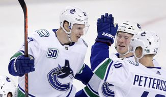 Vancouver Canucks' Tyler Myers, left, celebrates with Brock Boeser, center, and Elias Pettersson, from Sweden,  after his goal against the Calgary Flames during first-period NHL hockey game action in Calgary, Alberta, Sunday, Dec. 29, 2019. (Larry MacDougal/The Canadian Press via AP)