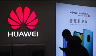 In this Dec. 11, 2018, file photo, a man browses his smartphone outside a Huawei store at a shopping mall in Beijing. Sen. Tom Cotton, Arkansas Republican, has introduced legislation preventing intelligence sharing with countries that permit Huawei to operate 5G networks. (AP Photo/Andy Wong) **FILE**