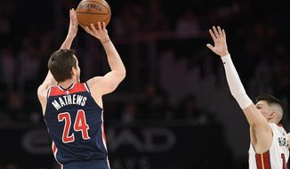Washington Wizards guard Garrison Mathews (24) shoots against Miami Heat guard Tyler Herro (14) during the first half of an NBA basketball game, Monday, Dec. 30, 2019, in Washington. (AP Photo/Nick Wass)