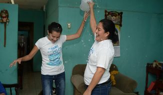 "Ivania Alvarez holds up an open jug of water to celebrates with Neyma Hernandez after their release from prison, at her home in Managua, Nicaragua, Monday, Dec. 30, 2019. The two belonged to the ""aguadores,"" a group of people who took water to protesters amid anti-government demonstrations starting in April 2018 over a social security overhaul which broadened to include demands for President Daniel Ortega's exit from office and early elections. (AP Photo/Oscar Navarrete)"