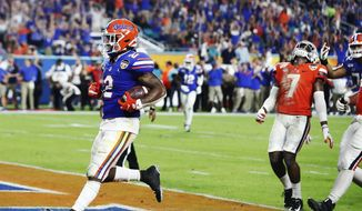 Virginia safety Chris Moore (7) reacts as Florida running back Lamical Perine (2) scores during the first half of the Orange Bowl NCAA college football game, Monday, Dec. 30, 2019, in Miami Gardens, Fla. (AP Photo/Brynn Anderson)