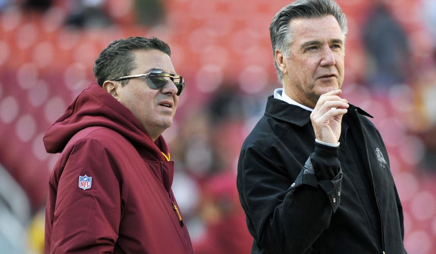 FILE - In this Oct. 21, 2018 file photo, Washington Redskins owner Dan Snyder, left, and team president Bruce Allen talk on the field prior to an NFL football game between the Dallas Cowboys and Washington Redskins,  in Landover, Md. Allen was fired Monday, Dec. 30, 2019, after a tumultuous and loss-filled decade with the NFL team once coached by his father. (AP Photo/Mark Tenally, File)