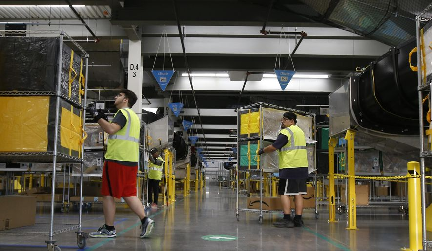 In this Dec. 17, 2019, photo Amazon workers bring stowed containers to their specific trucks after Amazon robots deliver separated packages by zip code at an Amazon warehouse facility in Goodyear, Ariz. (AP Photo/Ross D. Franklin)