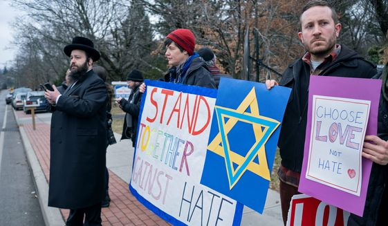 "Neighbors gather to show their support of the community near a rabbi's residence in Monsey, N.Y., Sunday, Dec. 29, 2019, following a stabbing Saturday night during a Hanukkah celebration. A knife-wielding man stormed into the home and stabbed five people as they celebrated Hanukkah in an Orthodox Jewish community north of New York City, an ambush the governor said Sunday was an act of domestic terrorism fueled by intolerance and a ""cancer"" of growing hatred in America. (AP Photo/Craig Ruttle) ** FILE **"