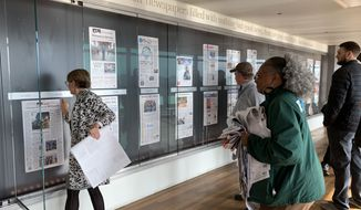 Newseum staffers change the display of the front pages of newspapers from around the world for the last time before the museum closes for its final day on Tuesday. Officials announced last year that the building would be sold to Johns Hopkins University. (Sophie Kaplan/The Washington Times)