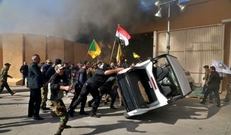 Protesters damage property inside the U.S. Embassy compound, in Baghdad, Iraq, Tuesday, Dec 31, 2019. Dozens of angry Iraqi Shiite militia supporters broke into the U.S. Embassy compound in Baghdad on Tuesday after smashing a main door and setting fire to a reception area, prompting tear gas and sounds of gunfire. (AP Photo/Khalid Mohammed)
