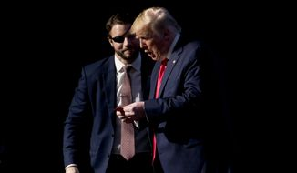 """Rep. Dan Crenshaw, R-Texas, left, comes on stage to hand President Donald Trump what he says is the """"No"""" vote card from Wednesday's House impeachment vote as Trump speaks at the Turning Point USA Student Action Summit at the Palm Beach County Convention Center in West Palm Beach, Fla., Saturday, Dec. 21, 2019. (AP Photo/Andrew Harnik)"""
