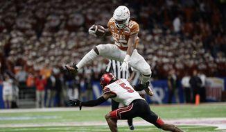 Texas running back Keaontay Ingram (26) leaps over Utah defensive back Tareke Lewis (5) during the second half of the Alamo Bowl NCAA college football game in San Antonio, Tuesday, Dec. 31, 2019. (AP Photo/Eric Gay)