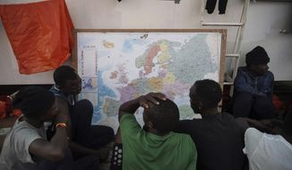 In this Sept. 23, 2019, file photo, rescued migrants look at a map of Europe aboard the Ocean Viking humanitarian ship as it sails in the Mediterranean Sea. The misery of migrants in Libya has spawned a thriving and highly lucrative business, in part funded by the EU and enabled by the United Nations, an Associated Press investigation has found. (AP Photo/Renata Brito)