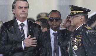 FILE - In this April 17, 2019 file photo, Brazil's President Jair Bolsonaro puts his hand over his heart as Army Commander Edson Leal Pujol salutes during the playing of the national anthem during a ceremony under the pouring rain to mark Army Day in Brasilia, Brazil. Heading into his second year as president, Bolsonaro has held firm to his combative culture-warrior policies while feuding with critics at home and abroad. (AP Photo/Eraldo Peres, File)