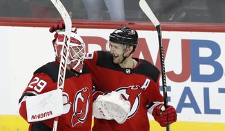 New Jersey Devils center Travis Zajac (19) celebrates with Devils goaltender Mackenzie Blackwood (29) after the Devils defeated the Boston Bruins in a shootout in an NHL hockey game, Tuesday, Dec. 31, 2019, in Newark, N.J. Devils defenseman Damon Severson scofred the game-deciding goal for a 3-2 victory over the Bruins. (AP Photo/Kathy Willens)