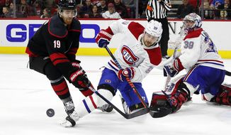 Montreal Canadiens' Tomas Tatar (90), of Slovakia, clears the puck in front of Carolina Hurricanes' Dougie Hamilton (19) during the second period of an NHL hockey game in Raleigh, N.C., Tuesday, Dec. 31, 2019. (AP Photo/Karl B DeBlaker)