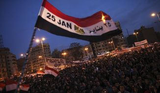 FILE -- In this Feb. 10, 2011 file photo, a flag is waved by anti-government protesters as they demonstrate in Tahrir Square in downtown Cairo, Egypt. Egypt's recent decision to transport ancient Pharaonic artifacts to Tahriri Square, the epicenter of Egypt's so-called Arab Spring uprising in 2011, has fueled fresh controversy over the government's handling of its archaeological heritage. Archaeologists and heritage experts fear vehicle exhaust will damage the ram-headed sphinxes and an obelisk, currently en route to their new home in Tahrir Square. (AP Photo/Tara Todras-Whitehill, File)