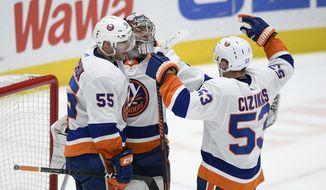 New York Islanders center Casey Cizikas (53), defenseman Johnny Boychuk (55) and goaltender Semyon Varlamov (40) celebrate after an NHL hockey game against the Washington Capitals, Tuesday, Dec. 31, 2019, in Washington. The Islanders won 4-3. (AP Photo/Nick Wass)