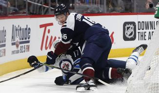 Colorado Avalanche defenseman Nikita Zadorov, front, knocks down Winnipeg Jets center Adam Lowry as he tries to control the puck during the second period of an NHL hockey game Tuesday, Dec. 31, 2019, in Denver. (AP Photo/David Zalubowski)