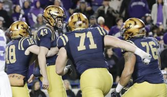 Navy's J.R. Osborn (18) grabs kicker Bijan Nichols (43) as Billy Honaker (71) and Kendel Wright (76) rush in to celebrate Nichols' winning 23-yard field goal against Kansas State in the final seconds of the fourth quarter of the Liberty Bowl NCAA college football game Tuesday, Dec. 31, 2019, in Memphis, Tenn. Navy won 20-17. (AP Photo/Mark Humphrey)