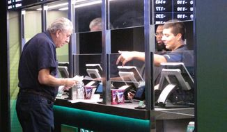 In this Oct. 8, 2019 photo, a man makes a sports bet at Resorts casino in Atlantic City, N.J. In November 2019, New Jersey's casinos and racetracks took in nearly $563 million worth of sports bets, a new monthly record. (AP Photo/Wayne Parry)