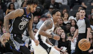 San Antonio Spurs' DeMar DeRozan, right, and Golden State Warriors' Marquese Chriss chase the ball during the first half of an NBA basketball game, Tuesday, Dec. 31, 2019, in San Antonio. (AP Photo/Darren Abate)