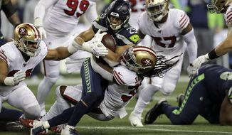 Seattle Seahawks running back Travis Homer (25) is brought down by San Francisco 49ers' Marcell Harris on a carry during the first half of an NFL football game, Sunday, Dec. 29, 2019, in Seattle. (AP Photo/Stephen Brashear)