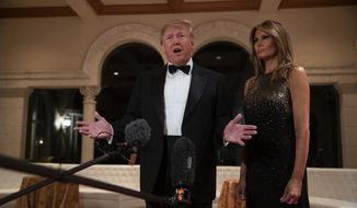 President Donald Trump speaks to reporters before his New Year's Eve party at his Mar-a-Lago property, as first lady Melania Trump listens, Tuesday, Dec. 31, 2019, in Palm Beach, Fla. (AP Photo/ Evan Vucci)