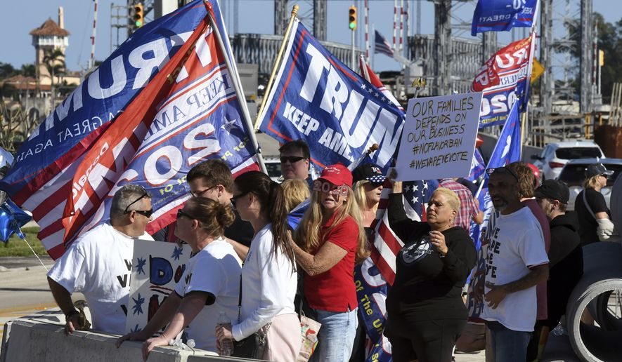 A group of people shows their banners towards President Donald Trump's motorcade on the way to Mar-a-Lago from the Trump International Golf Club in West Palm Beach, Fla., Wednesday, Jan. 1, 2020. (AP Photo/Jim Rassol)