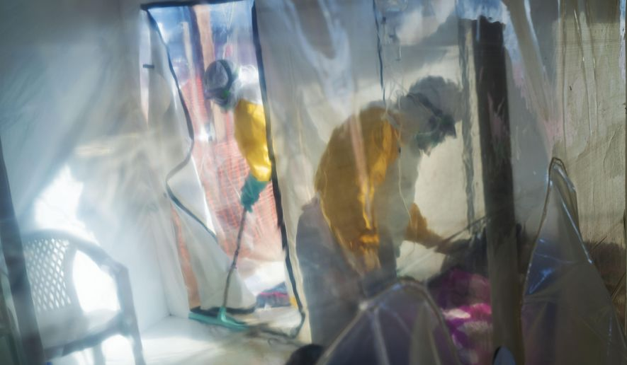 In this July 13, 2019, file photo, health workers wearing protective suits tend to an Ebola victim kept in an isolation cube in Beni, Congo. (AP Photo/Jerome Delay, File)
