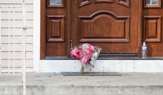 Flower bouquets rest on the doorstep of a rabbi's residence in Monsey, N.Y., Sunday, Dec. 29, 2019, following a stabbing Saturday night during a Hanukkah celebration. (AP Photo/Julius Constantine Motal)