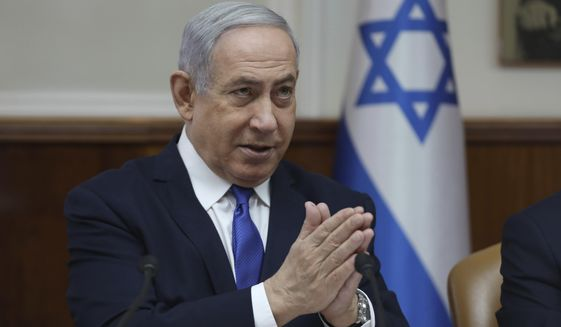 In this Sunday, Dec. 29, 2019 file photo, Israeli Prime Minister Benjamin Netanyahu attends the weekly cabinet meeting at his office in Jerusalem. Netanyahu said Monday that he would seek immunity from corruption charges, likely delaying any trial until after March elections, when he hopes to have a majority coalition that will shield him from prosecution. (Abir Sultan /Pool photo via AP, File) **FILE**