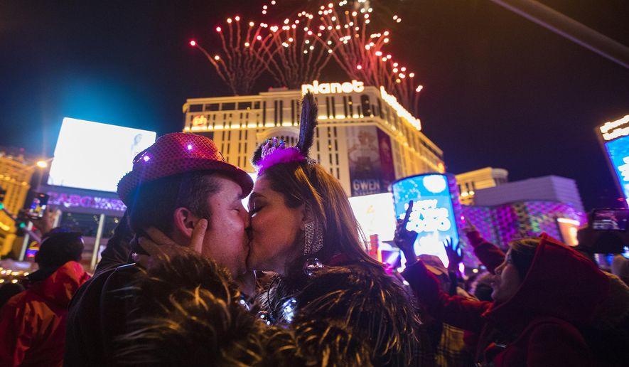 Moses Carpio, of Las Vegas, kisses his girlfriend Teresa Enriquez, of Juarez, on New Year's Eve in Las Vegas, Wednesday, Jan. 1, 2020. (Rachel Aston/Las Vegas Review-Journal via AP)