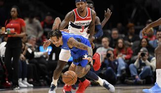 Orlando Magic guard Markelle Fultz, front, chases a loose ball in front of Washington Wizards guard Bradley Beal (3) during the first half of an NBA basketball game Wednesday, Jan. 1, 2020, in Washington. (AP Photo/Nick Wass)