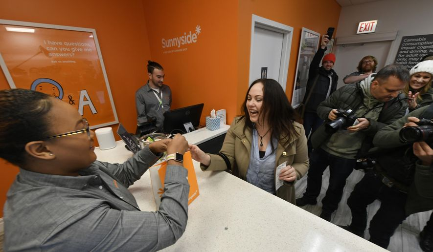 Jackie Ryan, right, of Forest Park, Ill., becomes the first person in Illinois to purchase recreational marijuana as she buys products from employee Brea Mooney left, at Sunnyside dispensary Wednesday, Jan. 1, 2020, in Chicago. (AP Photo/Paul Beaty) ** FILE **