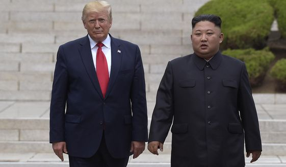 FILE - In this June 30, 2019, file photo, U.S. President Donald Trump, left, meets with North Korean leader Kim Jong Un at the North Korean side of the border at the village of Panmunjom in Demilitarized Zone. Kim's threat to show the world a new strategic weapon and possibly resume long-range missile tests is another dramatic turn in his high-stakes summitry with President Donald Trump. (AP Photo/Susan Walsh, File)