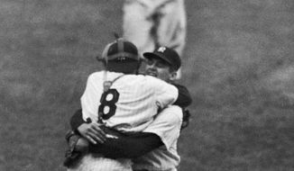 In this Oct. 8, 1956, file photo, New York Yankees catcher Yogi Berra leaps into the arms of pitcher Don Larsen after Larsen struck out the last Brooklyn Dodgers batter to complete his perfect game during Game 5 of the World Series in New York. Larsen, the journeyman pitcher who reached the heights of baseball glory in 1956 for the Yankees when he threw a perfect game and only no-hitter in World Series history, died Wednesday, Jan. 1, 2020. He was 90. (AP Photo/File)