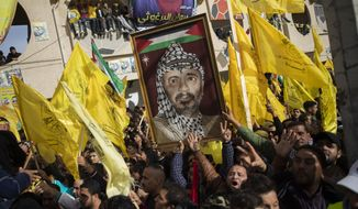 A Palestinian carries a picture of the late Palestinian leader Yasser Arafat, during a rally marking the 55th anniversary of the Fatah movement founding, in Gaza City, Wednesday, Jan. 1, 2020. Fatah is a secular Palestinian party and former guerrilla movement founded by Arafat, in Gaza City, Wednesday, Jan. 1, 2020. (AP Photo/Khalil Hamra)