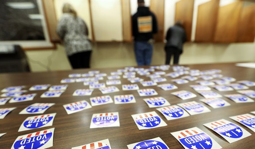 In this Nov. 6, 2018, file photo, people vote at Jamestown Town Hall in Kieler, Wis. Conservatives are asking a judge to find the Wisconsin Elections Commission in contempt for not immediately purging more than 200,000 voters from the rolls. A judge last month ordered the purge of voters who may have moved and didn't respond within 30 days to a notification sent by the elections commission in October 2019. (Nicki Kohl/Telegraph Herald via AP, File)